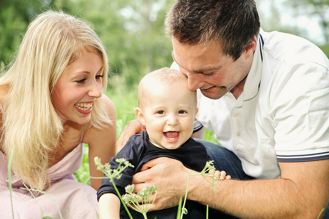 Happy young parents playing with baby boy